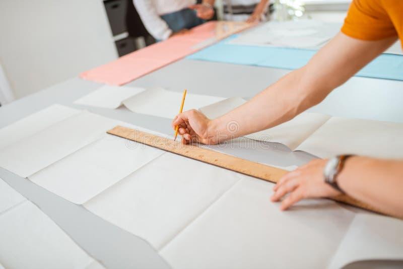 Mãos novas dos desenhadores de moda que esboçam um teste padrão costurando foto de stock royalty free