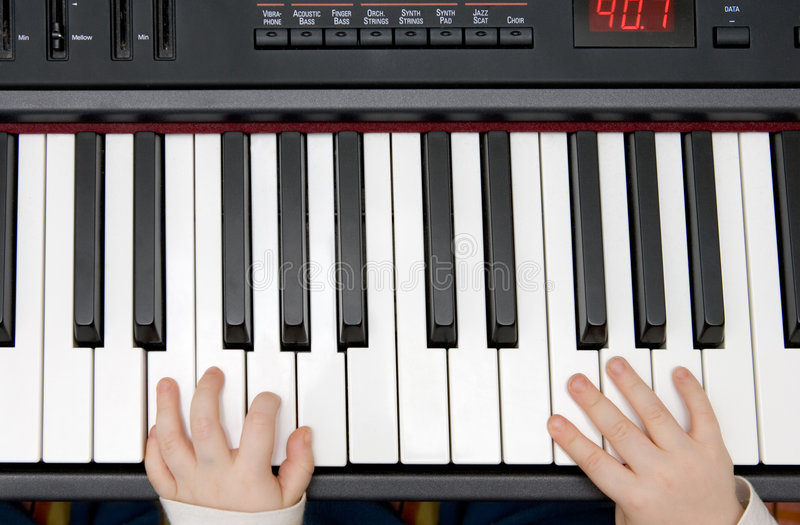 Mãos novas dos meninos em um piano ou em um teclado eletrônico fotografia de stock