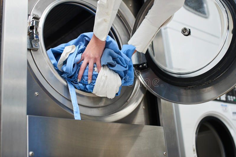 Mãos para carregar a lavanderia na máquina de lavar foto de stock
