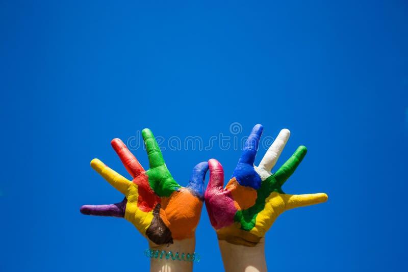 Mãos pintadas das crianças no backgrobnd do céu azul fotos de stock royalty free