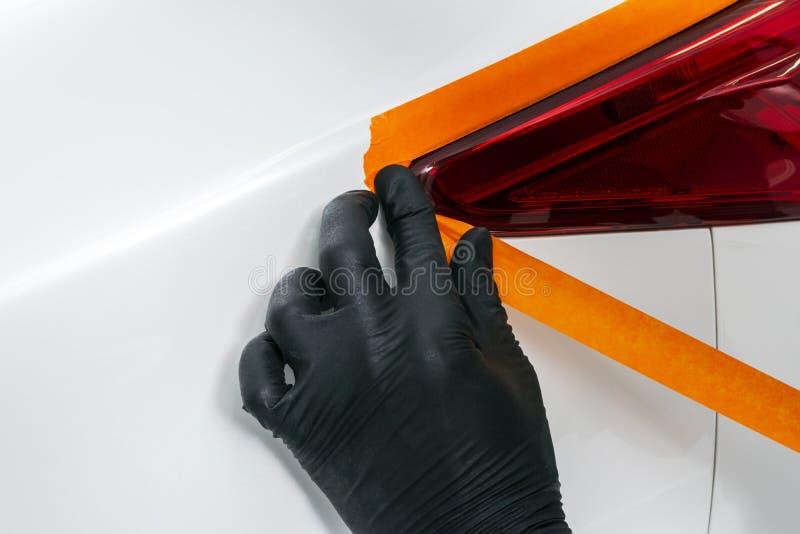 Mãos polonesas do trabalhador da cera do carro que aplicam a fita protetora nas luzes traseiras antes de lustrar Farol lustrando  foto de stock