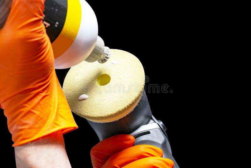 Mãos polonesas do trabalhador da cera do carro que guardam o polisher e o polimento Fim acima do polisher guardando à mão e de ap foto de stock royalty free