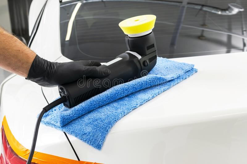 Mãos polonesas do trabalhador da cera do carro que guardam o polisher e o polimento Fim acima do polisher guardando à mão do carr imagens de stock