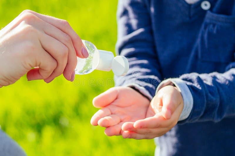 Mãos próximas da mãe aplicam gel antibacteriano antisséptico na mão do filho no parque num fundo verde fotos de stock