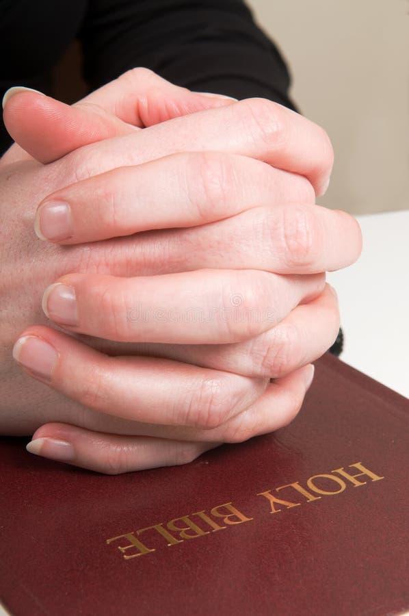 Mãos Praying na Bíblia foto de stock