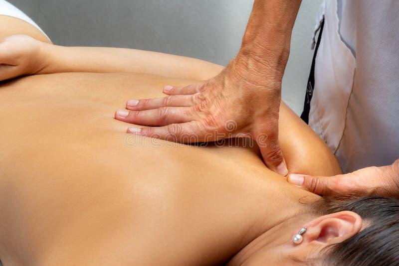 Mãos pressionando com polegares no ombro feminino imagem de stock