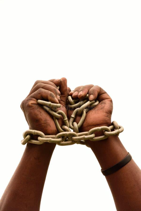 Mãos pretas africanas nas correntes fotografia de stock