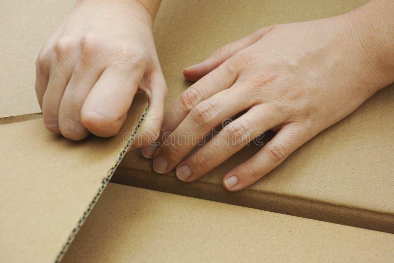 Mãos que abrem a caixa de cartão imagem de stock