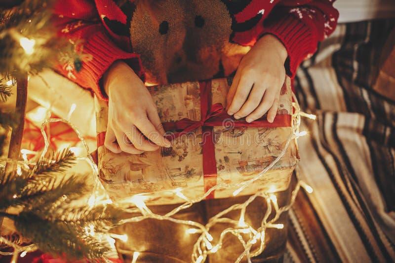 Mãos que abrem a caixa de presente do Natal sobre no christma bonito dourado imagem de stock royalty free