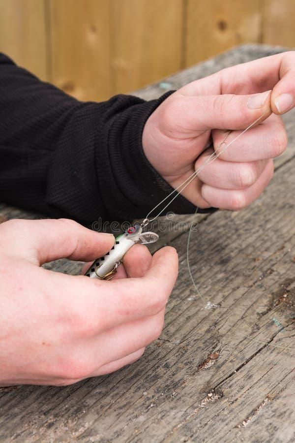 Mãos que amarram a atração da pesca imagens de stock royalty free