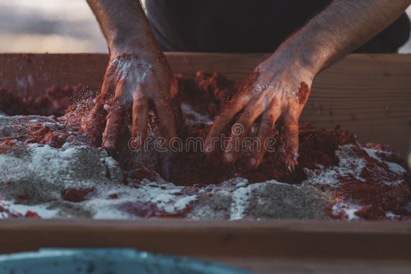 Mãos que amassam a carne crua com especiarias para fazer o sobrasada imagem de stock