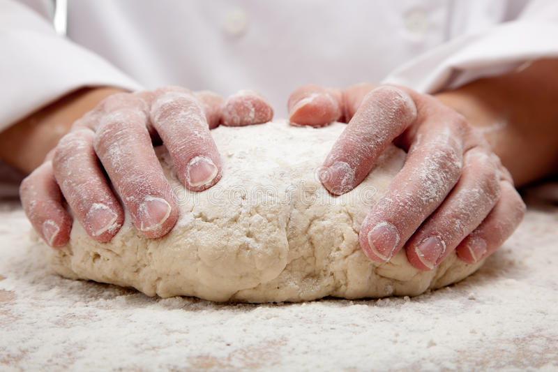 Mãos que amassam a massa de pão de pão fotografia de stock royalty free