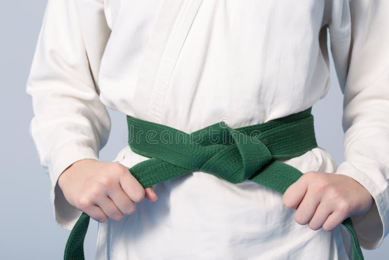 Mãos que apertam o cinto verde em um adolescente vestido no quimono imagens de stock royalty free