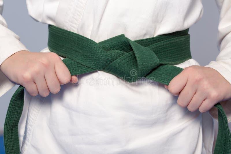 Mãos que apertam o cinto verde em um adolescente vestido no quimono fotografia de stock royalty free