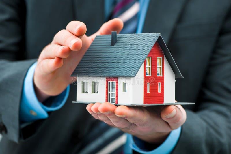 Mãos que apresentam uma casa pequena imagem de stock