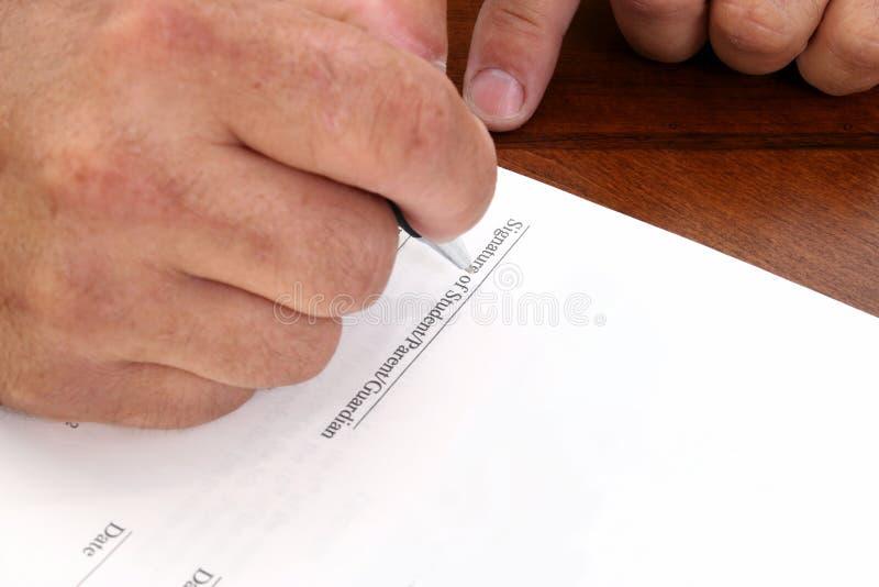 Mãos que assinam contrato relacionado da escola fotografia de stock