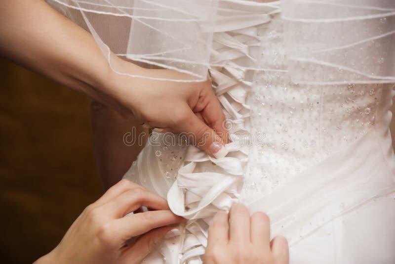 Mãos que atam o vestido das noivas fotografia de stock