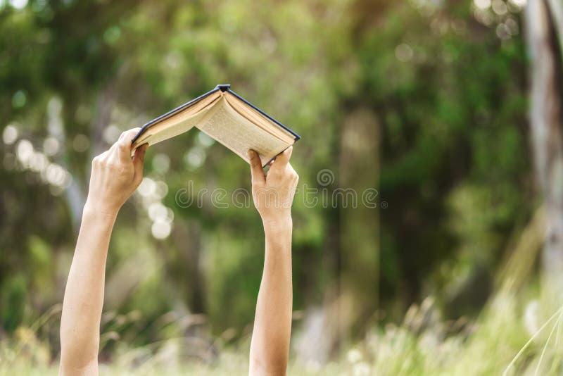 Mãos que aumentam um livro até lido imagem de stock royalty free