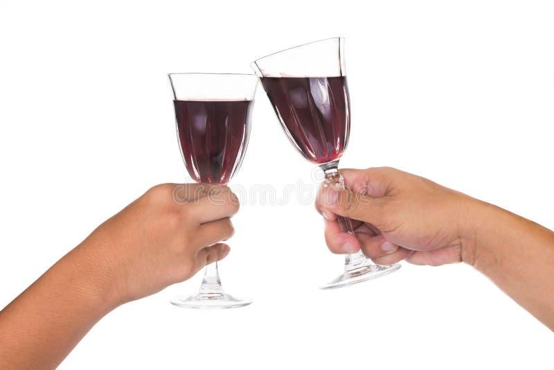 Mãos que brindam o vinho tinto nos cristais imagem de stock