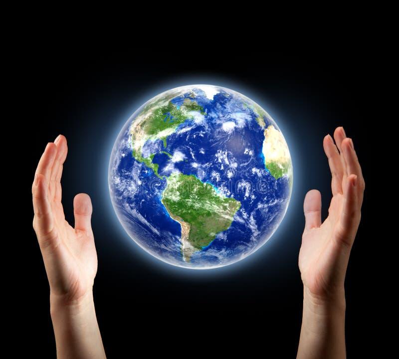 Mãos que cercam a terra do planeta foto de stock royalty free
