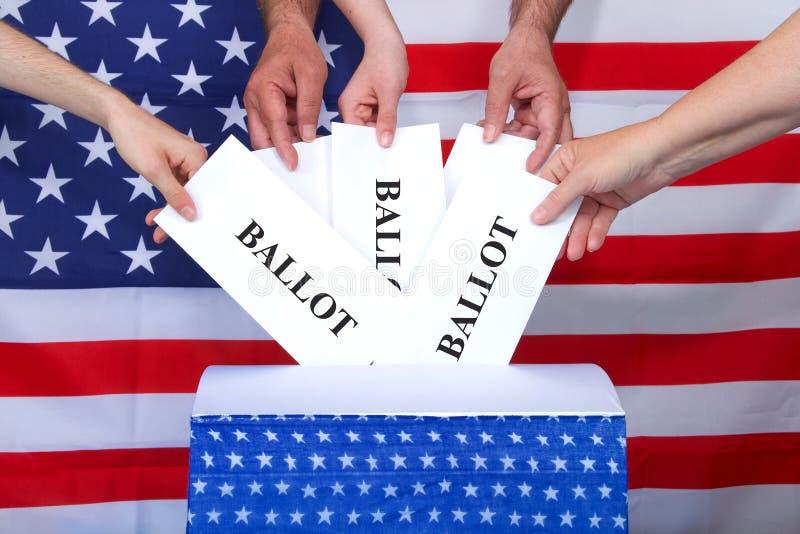 Mãos que colocam cédulas na caixa com bandeira americana atrás fotos de stock