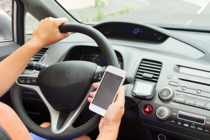 Mãos que conduzem e que guardam um telefone fotografia de stock