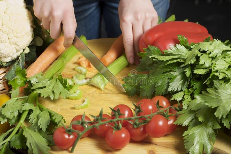 Mãos que cortam vegetais imagens de stock royalty free