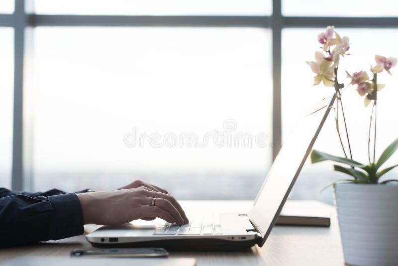 Mãos que datilografam em um teclado do portátil Um homem trabalha em um escritório em seu local de trabalho imagem de stock