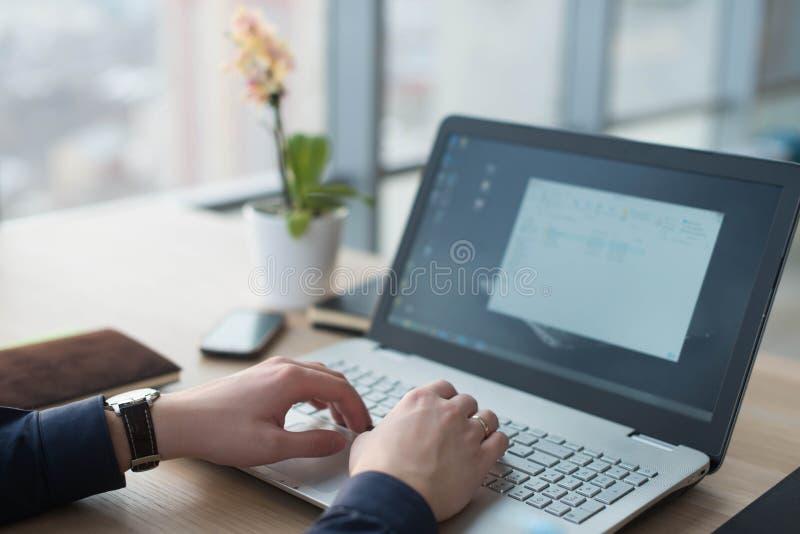 Mãos que datilografam em um teclado do portátil Um homem trabalha em um escritório em seu local de trabalho imagem de stock royalty free