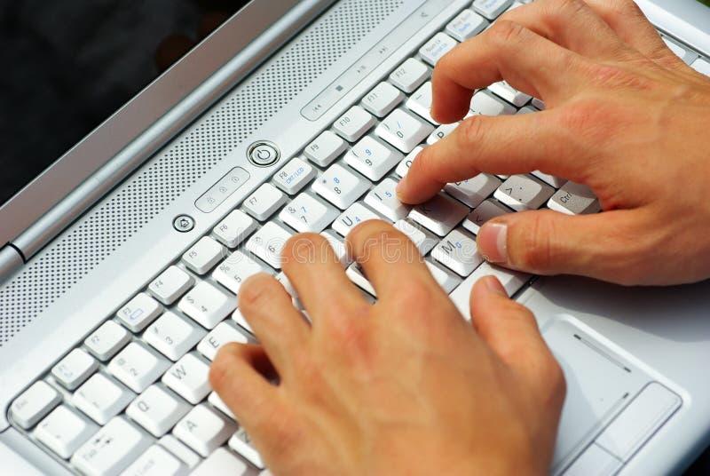 Mãos que datilografam no portátil foto de stock