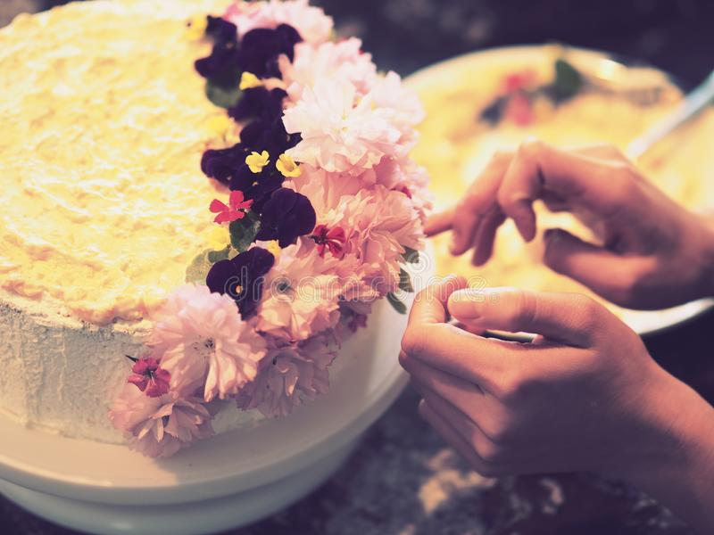 Mãos que decoram um bolo com flores fotos de stock