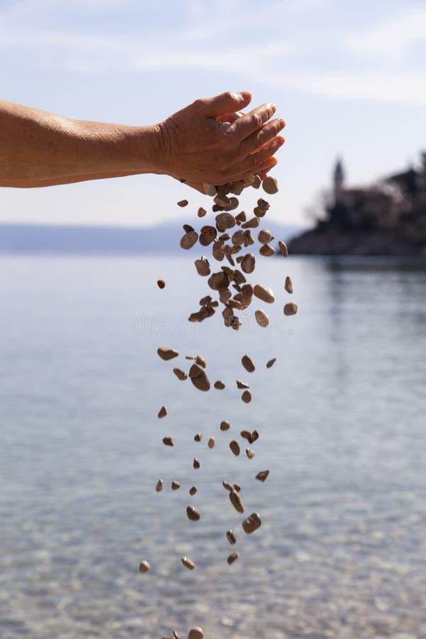 Mãos que deixam cair pedras pequenas no mar fotos de stock