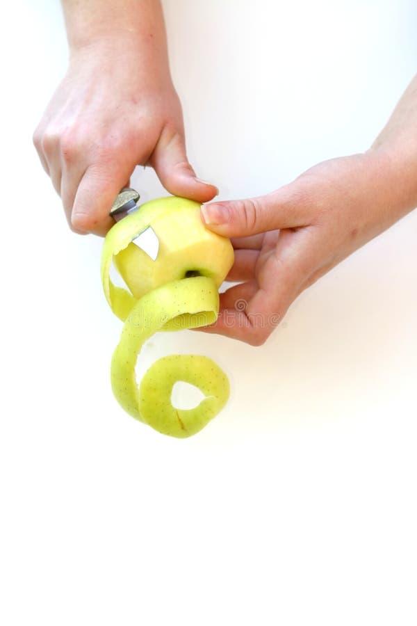 Mãos que descascam uma maçã fotos de stock