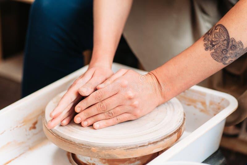 Mãos que encontram-se na roda de oleiro vazia fotografia de stock royalty free