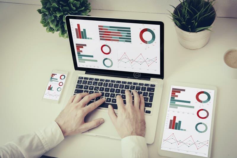 mãos que escrevem em um portátil com as finanças da tabuleta e do telefone gráficas imagem de stock royalty free