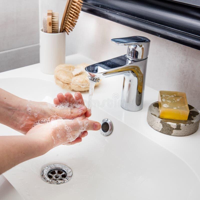 Mãos que espumam com o sabão, limpando com o água da torneira para a higiene imagem de stock royalty free