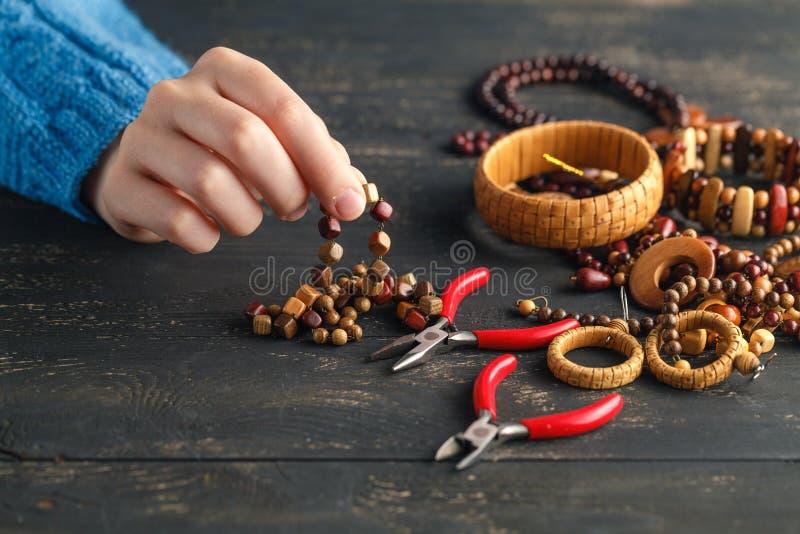 Mãos que fazem brincos de madeira handcrafted, fim acima fotografia de stock