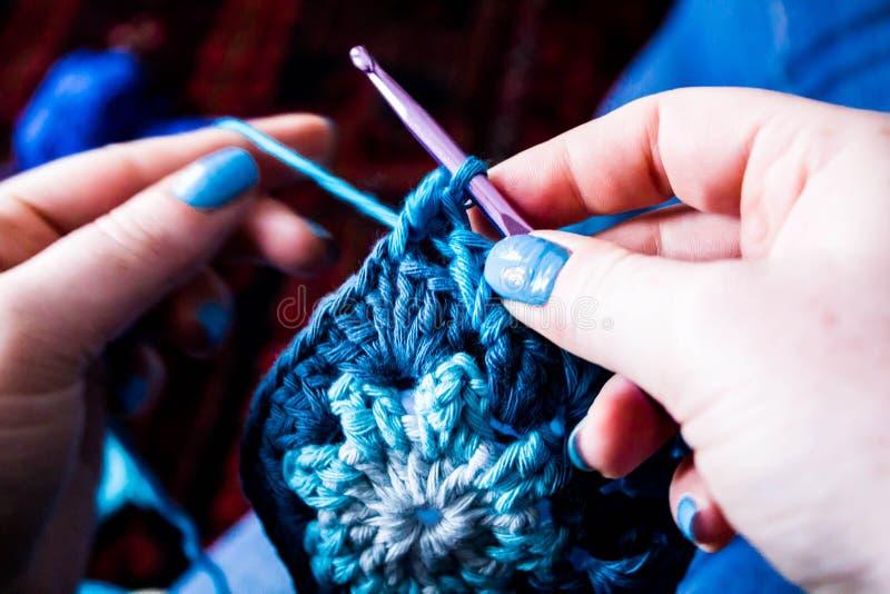 Mãos que fazem malha/quadrados avó do crochê fotografia de stock royalty free