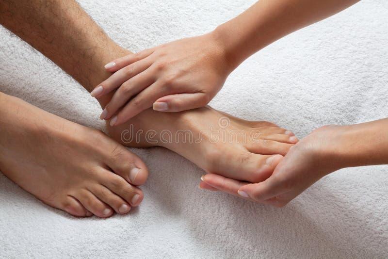 Mãos que fazem massagens os pés foto de stock royalty free