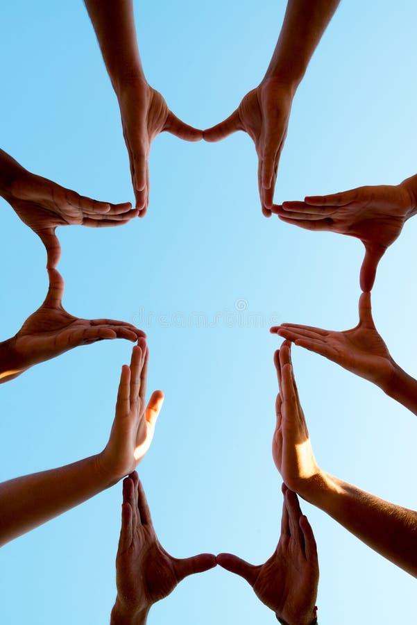 Mãos que fazem uma cruz imagem de stock royalty free