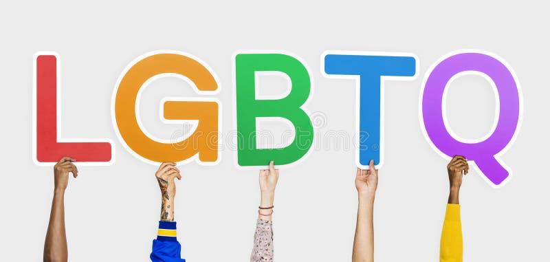Mãos que guardam a abreviatura LGBTQ fotos de stock