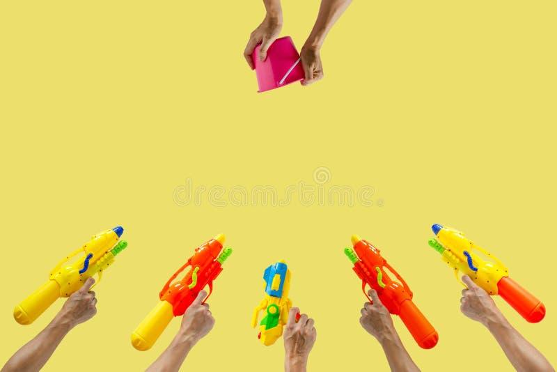Mãos que guardam a arma e a cubeta de água para o festival da água ou do Songkran imagens de stock