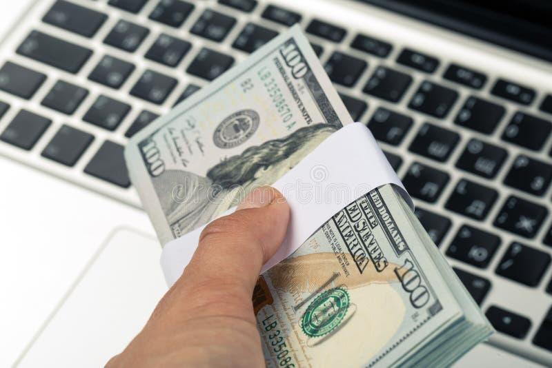 Mãos que guardam as cédulas do dólar, teclado do portátil no fundo fotografia de stock royalty free