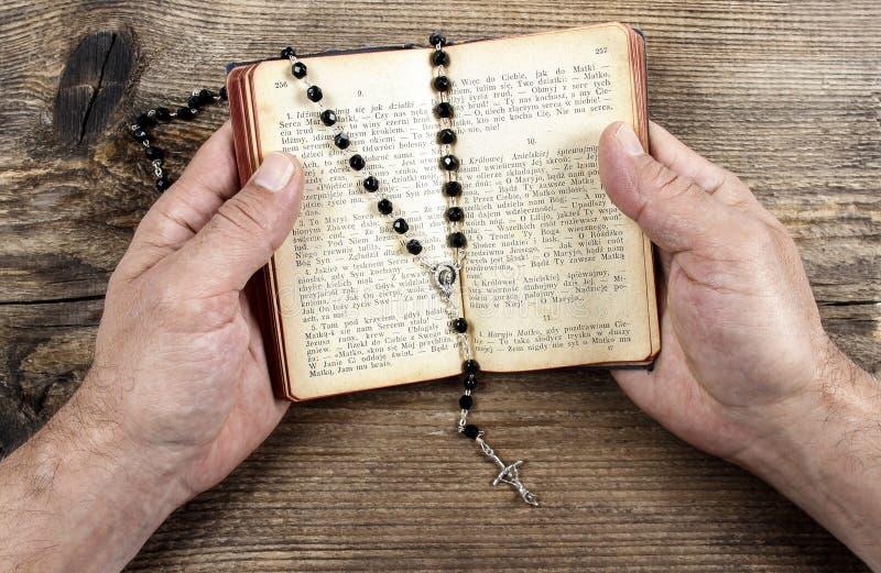 Mãos que guardam a Bíblia e que rezam com um rosário imagens de stock royalty free