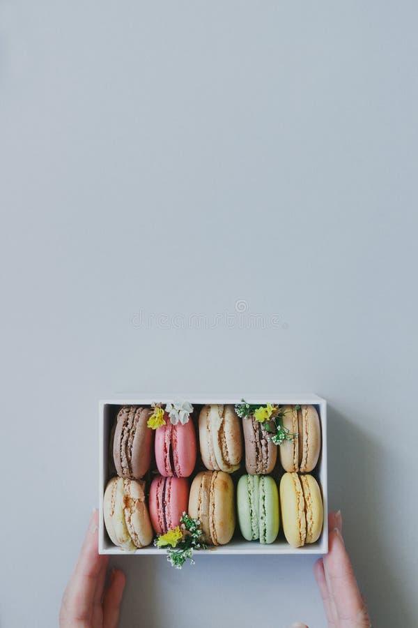 Mãos que guardam a caixa de presente com os bolinhos de amêndoa deliciosos na luz - fundo azul, vista superior fotos de stock