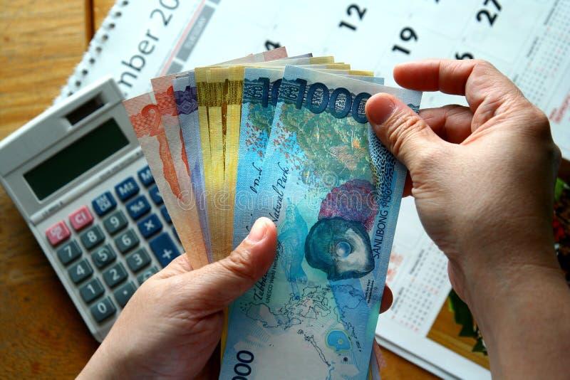 Mãos que guardam contas de dinheiro e uma calculadora e um calendário imagens de stock royalty free