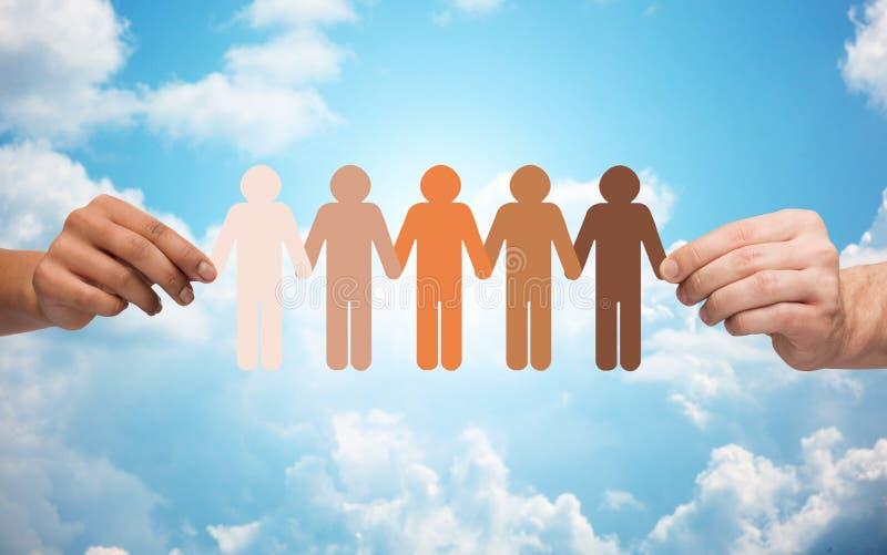 Mãos que guardam a corrente do pictograma dos povos sobre o céu imagens de stock