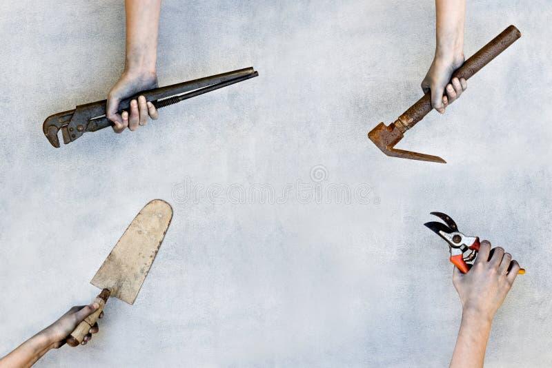 Mãos que guardam ferramentas da construção no fundo cinzento fotos de stock