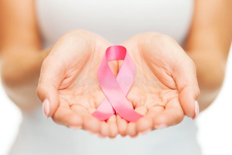 Mãos que guardam a fita cor-de-rosa da conscientização do câncer da mama fotografia de stock