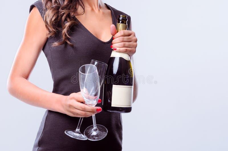 Mãos que guardam a garrafa de flautas do vinho espumante e de champanhe imagens de stock